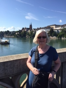 Ann on a bridge over the Rhine river in Basel with the Cathedral in the distance