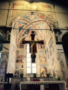 Basilica de San Francesco in Arezzo with a suspended cross in front of the altar which is surrounded by frescoes painted by Piero della Francesca