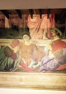 Just part of Piero della Francesca's painting of the resurrection because the upper half is being restored and is covered by a platform under which I took this photo  Francesca painted himself as the second soldier from left asleep.