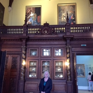Ann in the Baronial Dining Hall showing the music gallery and more porcelain and paintings