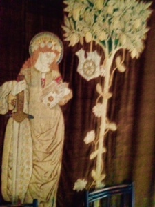 Textile wall hanging of St Catherine worked by Jane Morris in Kelmscott Manor