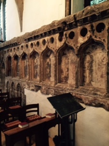 The old mediaeval stone reredos that used to stand behind the high altar now part of the wall of the side aisle