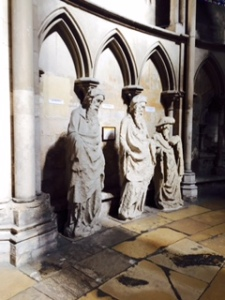 Three of about 30 ancient and very weathered statues  lining the side aisles of Rouen cathedral