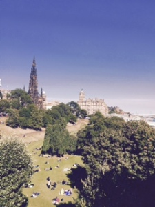View from the Art Gallery square in Edinburgh with locals sun-baking on the lawns in the